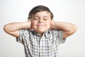 Boy (3-5) covering ears, eyes closed, close-up